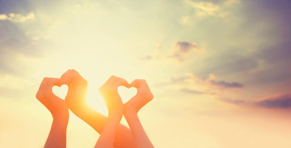 Zwei Handpaare bilden Herzen vor Sonne